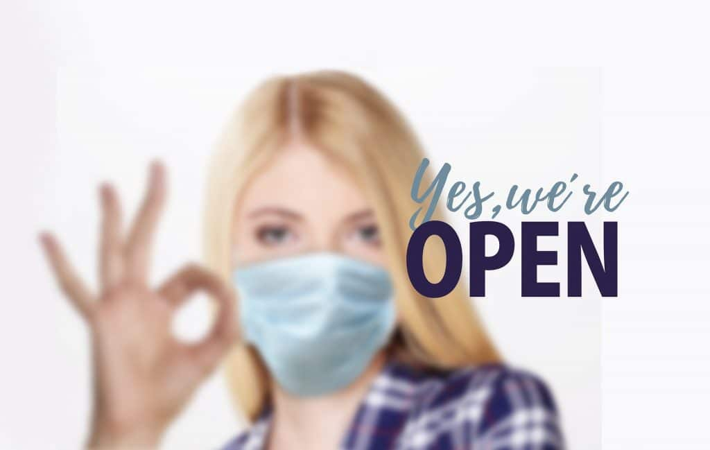 "Photo of lady showing OK hand sign and wording saying, ""yes we're open"""